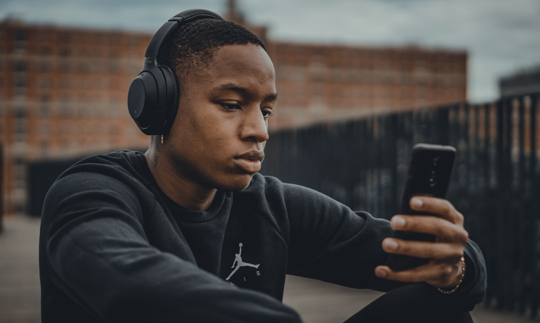 Seated man listening music on this phone