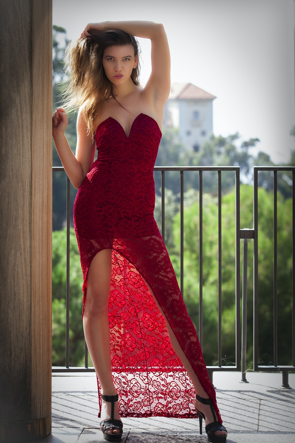 woman in red spaghetti strap dress standing near brown wooden fence during daytime
