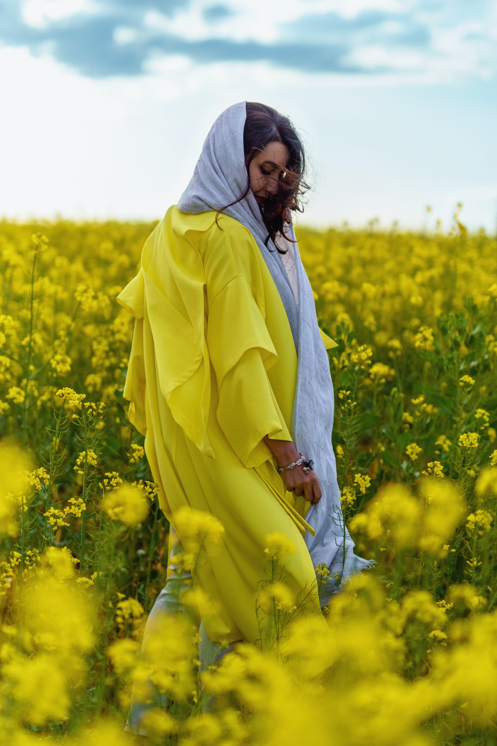 woman in white robe standing on yellow flower field during daytime