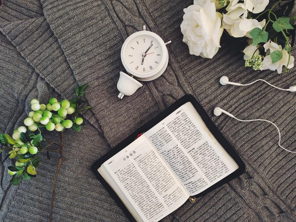 white book beside white round analog wall clock