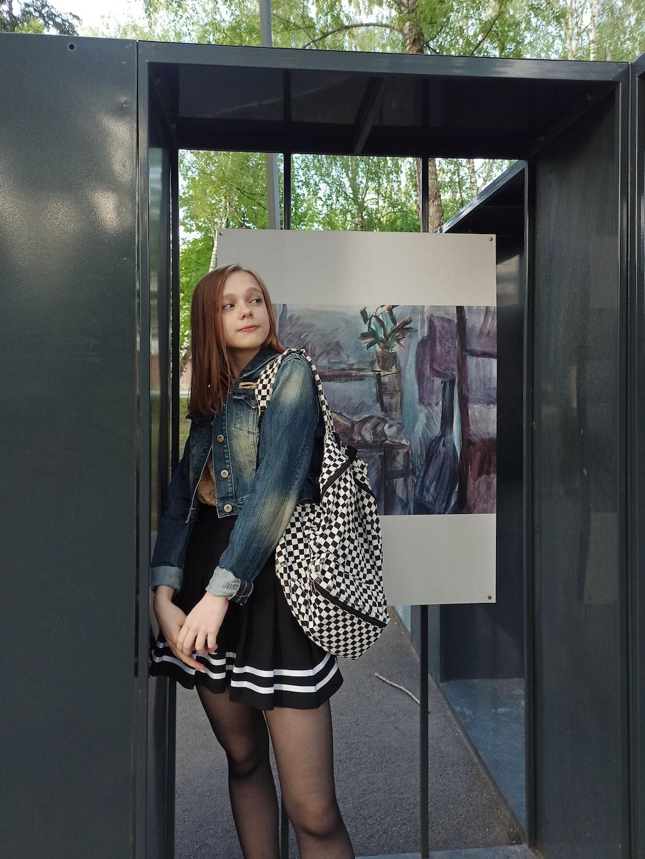 woman in black and white polka dot dress standing beside glass window