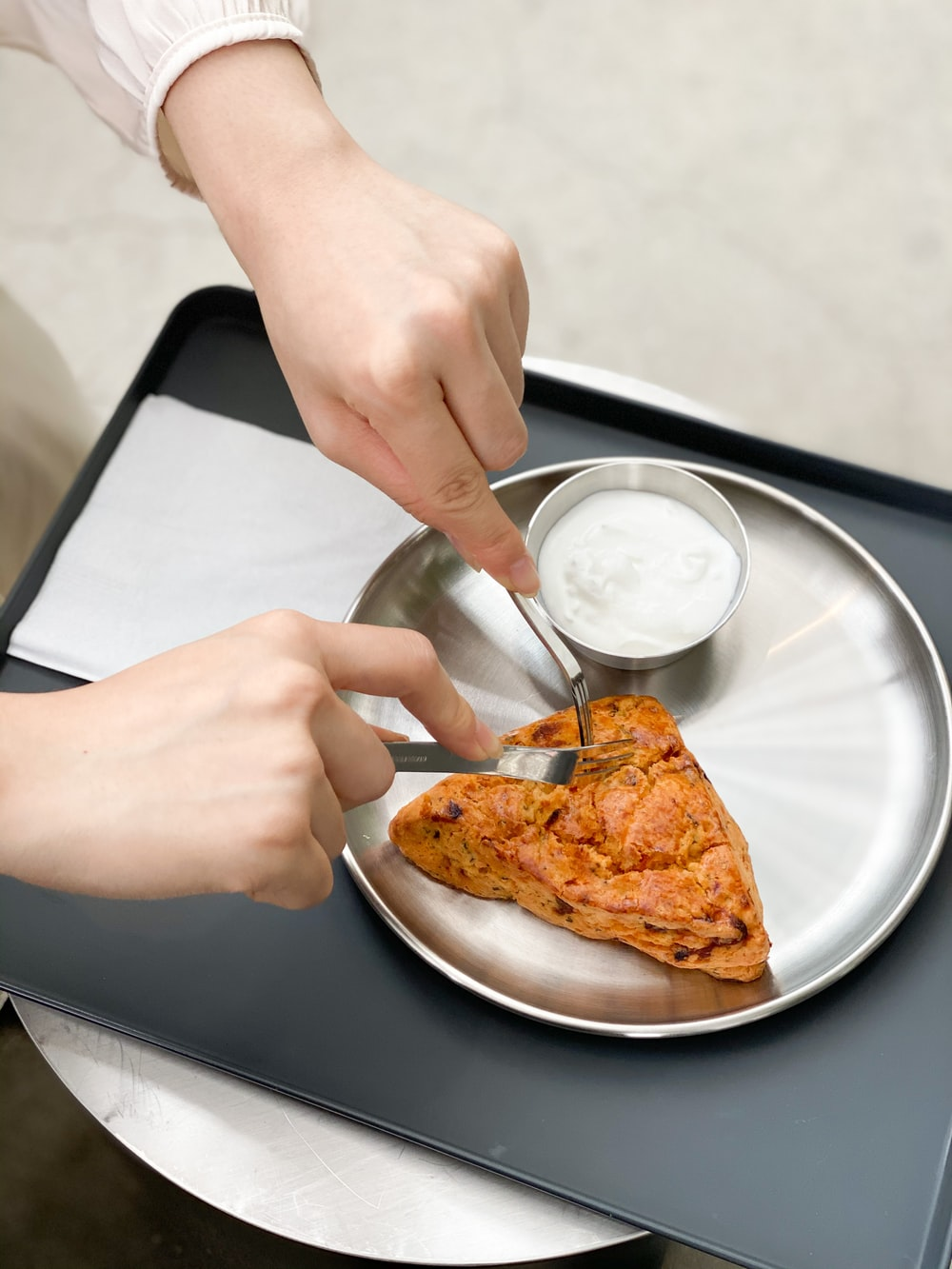 person holding stainless steel spoon and fork on white ceramic plate