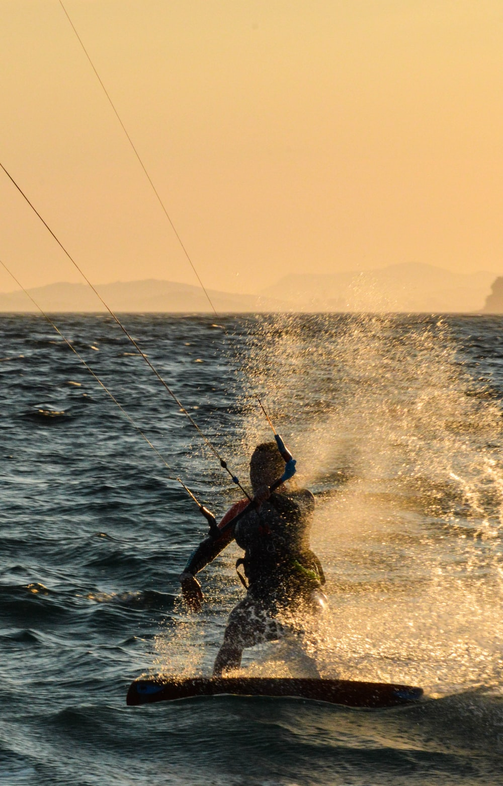 man in black wet suit holding fishing rod on sea during daytime