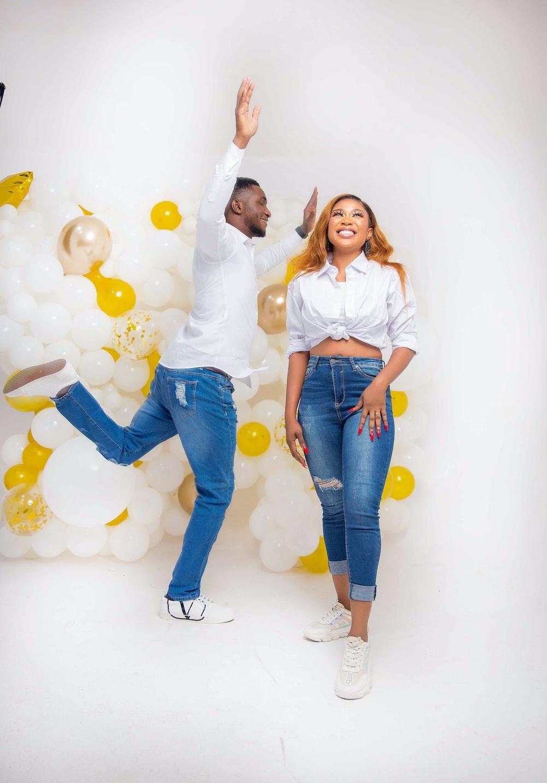 girl in white long sleeve shirt and blue denim jeans standing beside balloons