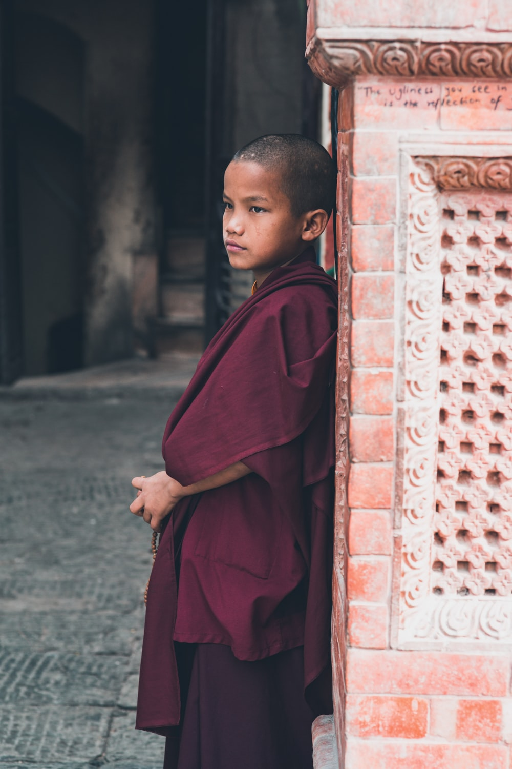 boy in red robe standing near brown brick wall during daytime