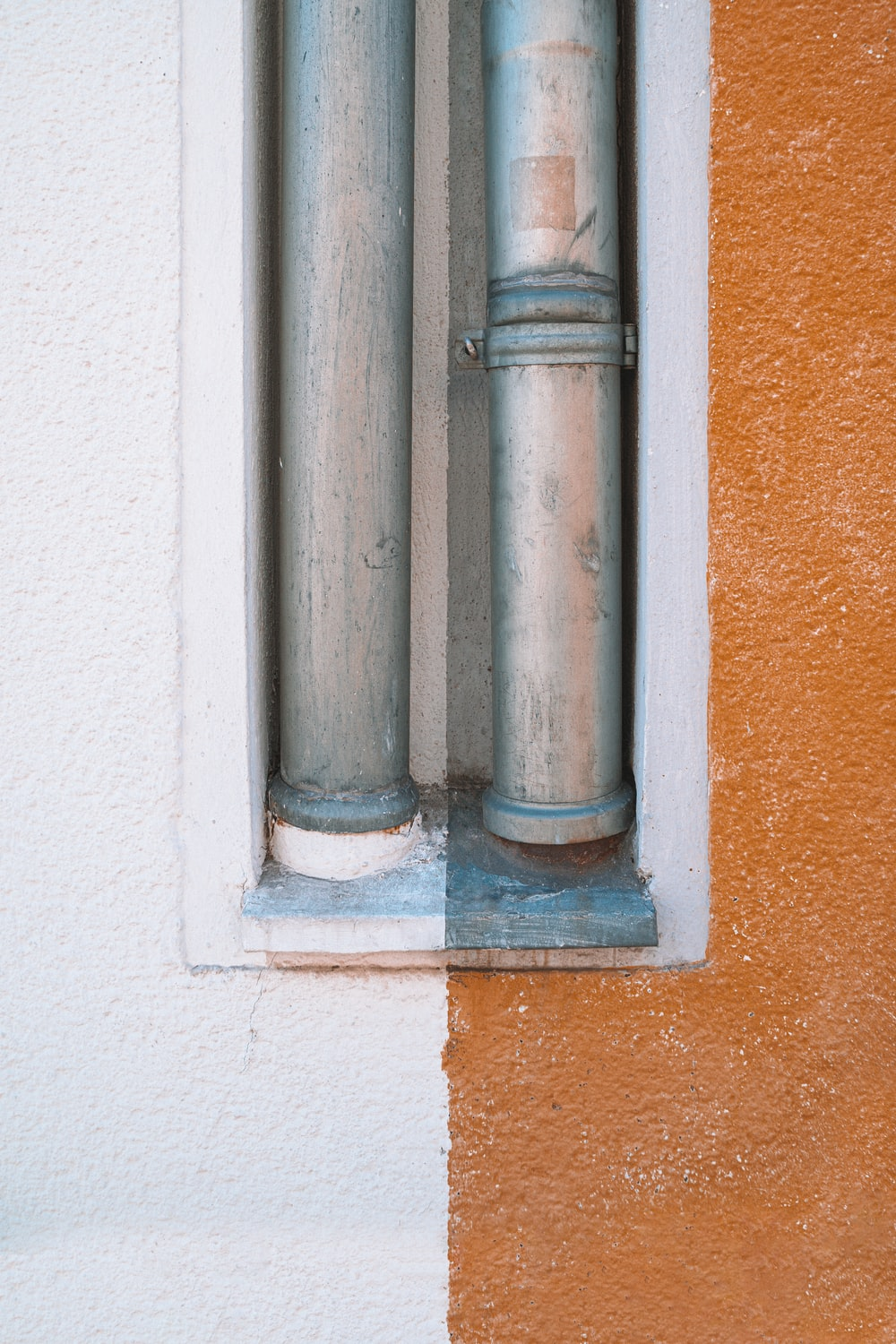 white concrete wall with gray metal pipe