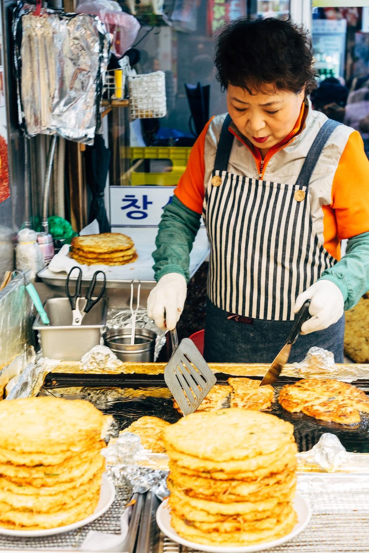 woman in white apron holding black spatula