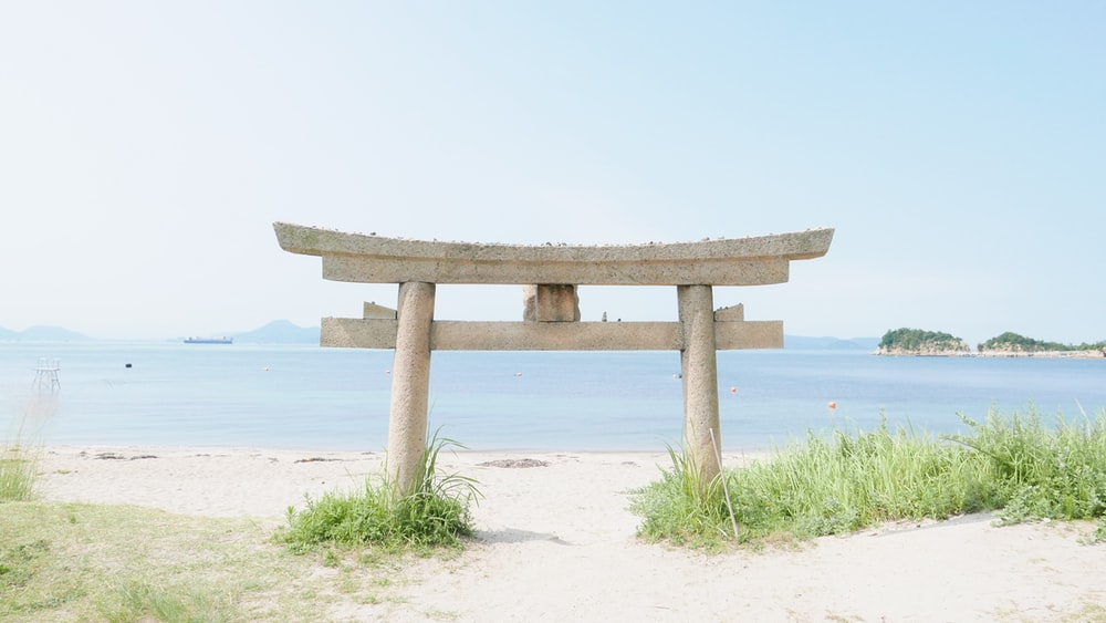 brown wooden stand on white sand near body of water during daytime