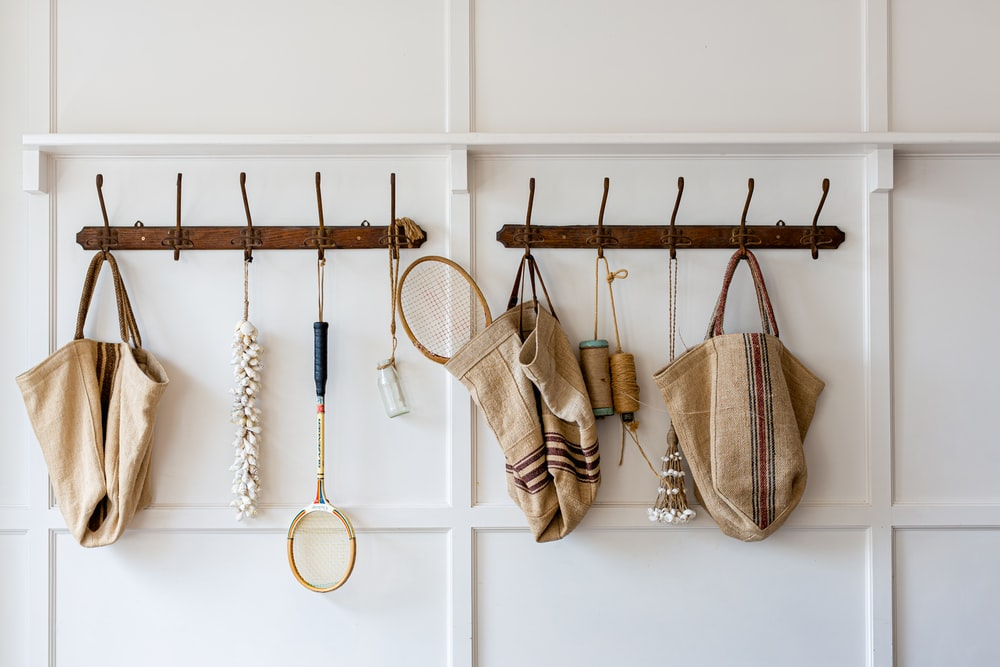 brown and white sling bags hanged on white wooden wall