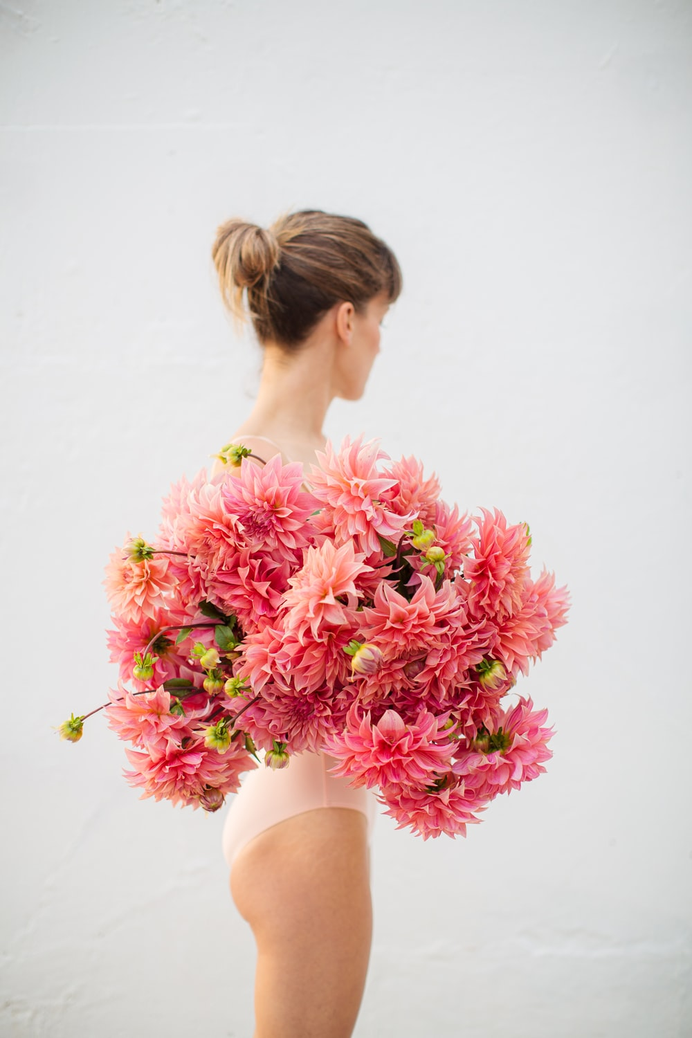woman in white tank top holding pink flowers