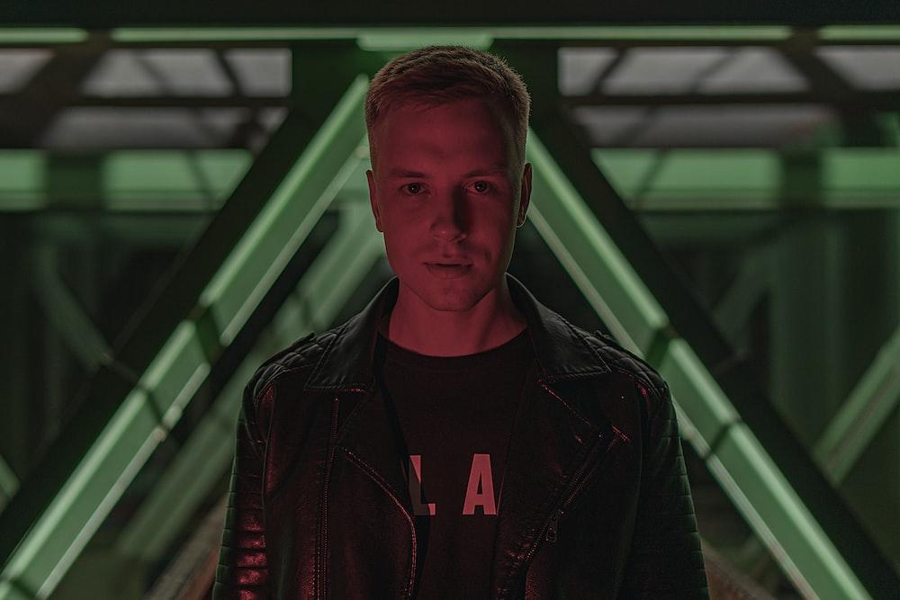 man in black leather jacket standing near glass window