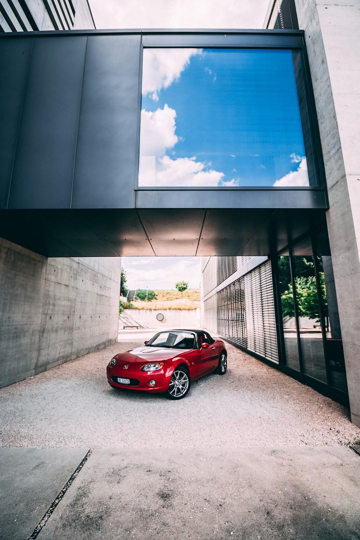 red ferrari 458 italia parked beside gray concrete building
