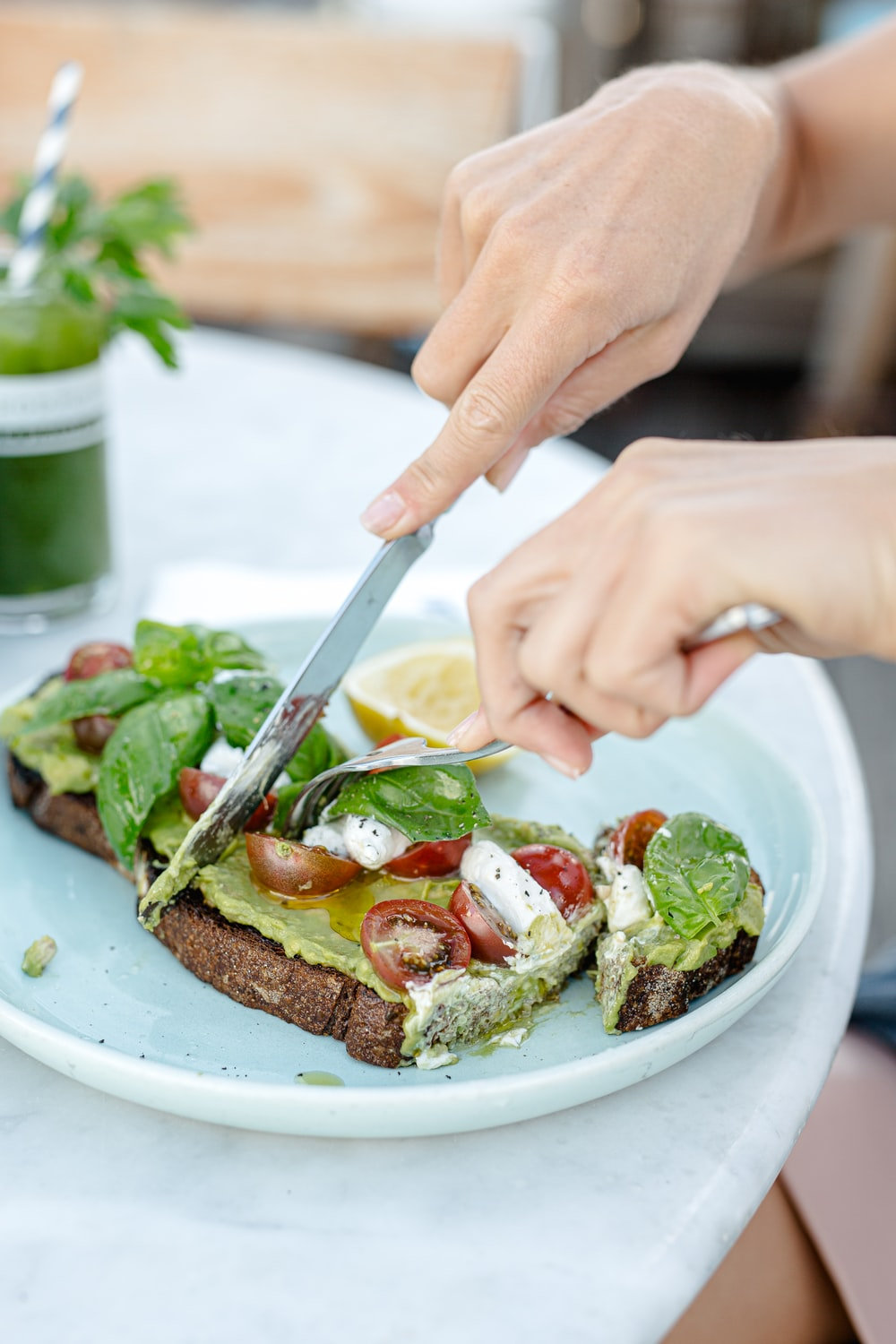 person holding knife slicing bread with vegetable on white ceramic plate