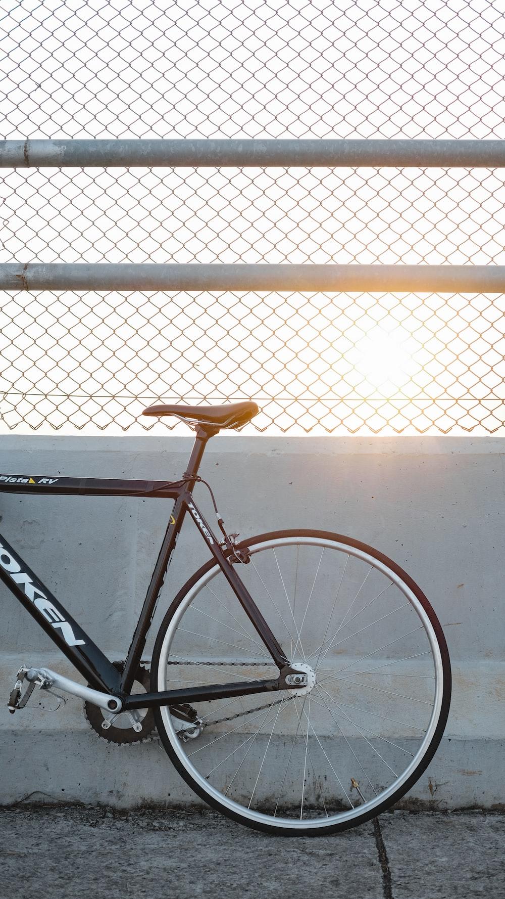 orange and black road bike leaning on white metal fence