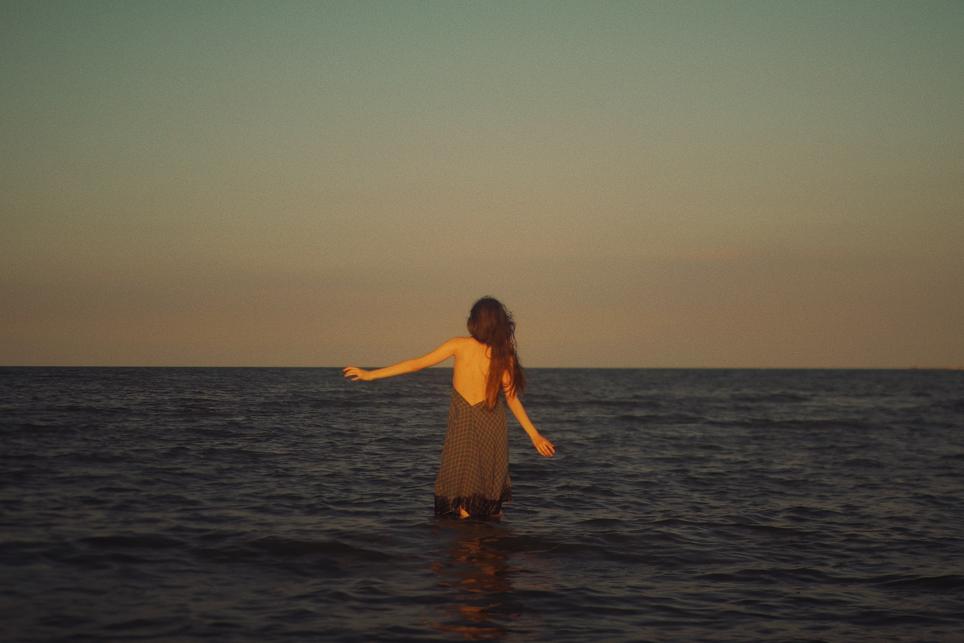 woman in black dress standing on water during sunset