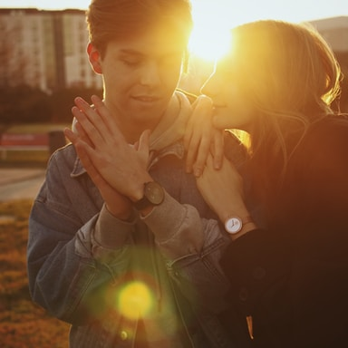 man in black jacket kissing woman in gray jacket during sunset
