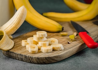 yellow banana fruit on brown wooden chopping board