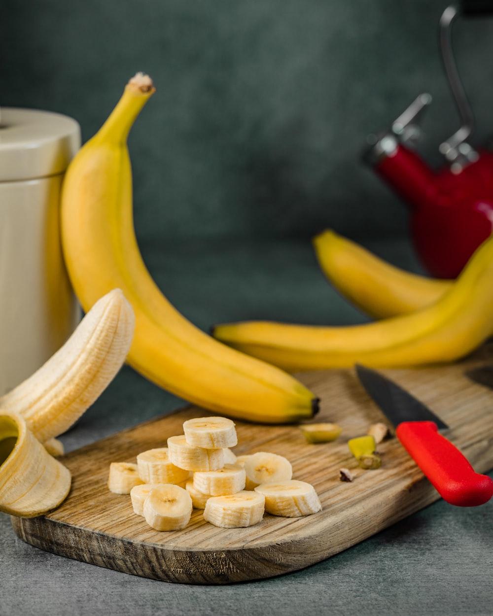 yellow banana fruit on brown wooden chopping board