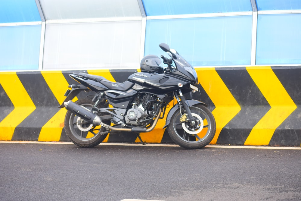 yellow and black sports bike parked beside white wall