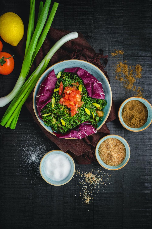 vegetable salad in bowl beside sliced bread and orange fruit