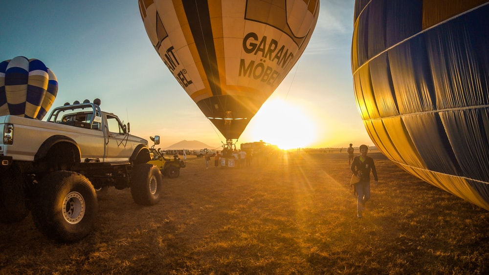 people standing near hot air balloons during sunset