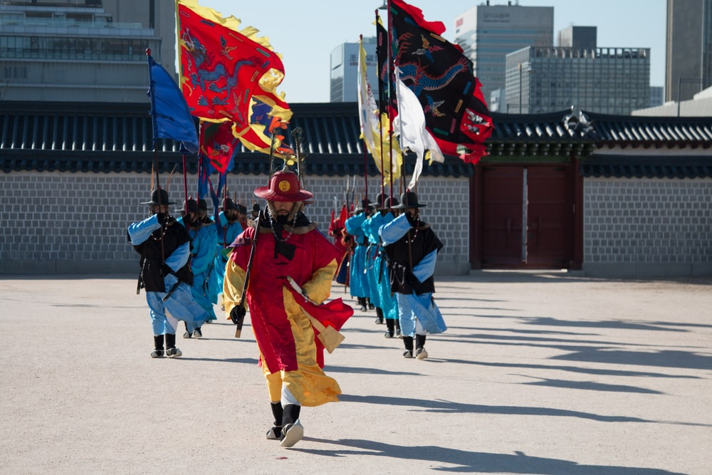 people in blue and red traditional dress holding flags during daytime