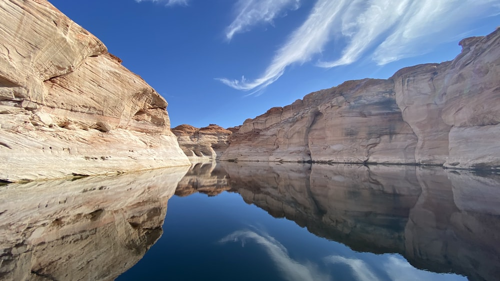 brown rock formation beside body of water under blue sky during daytime