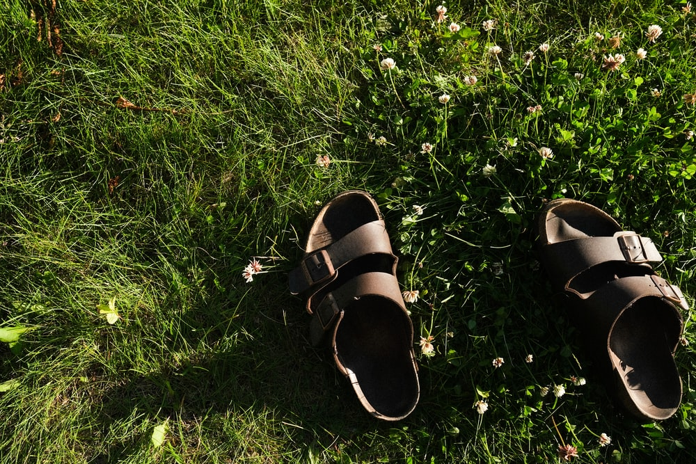 black and brown leather sandals on green grass