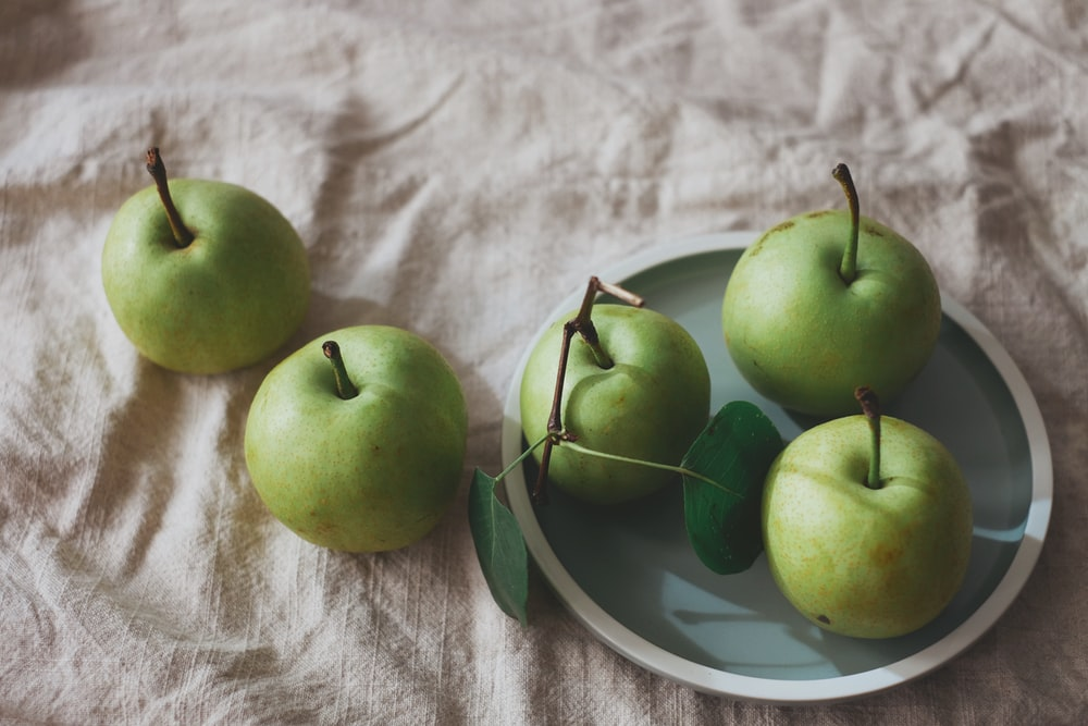 green apples on white and blue ceramic plate