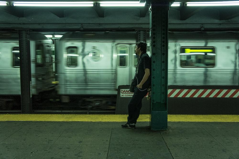 man in black jacket standing beside white train