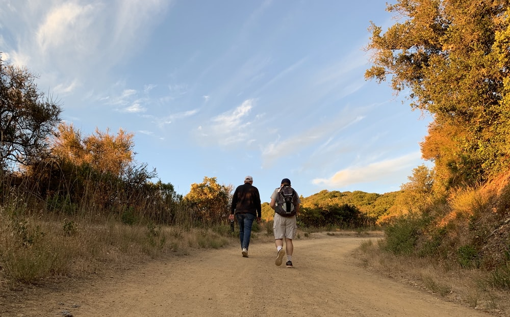 man and woman walking on dirt road between green grass field during daytime