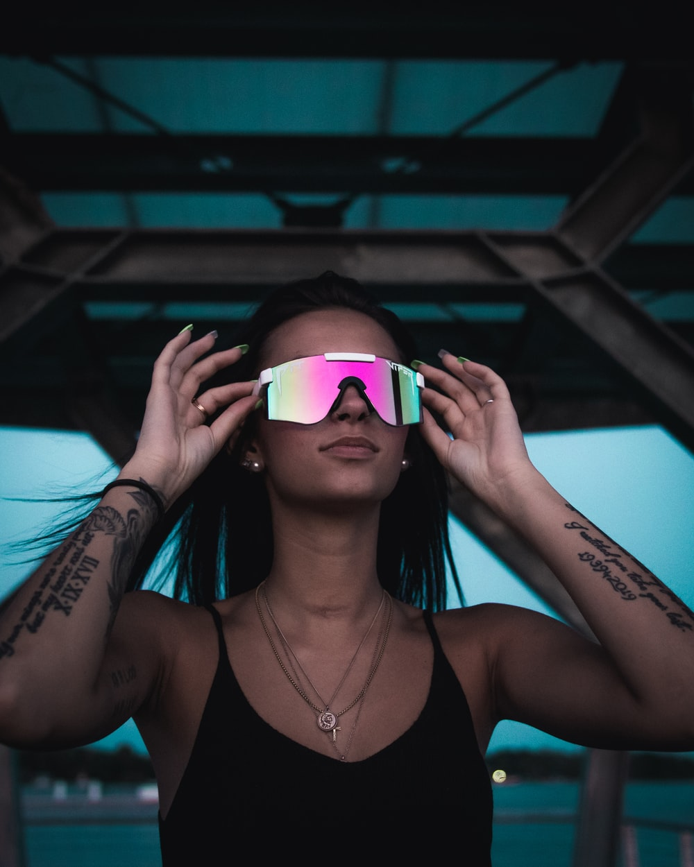 woman in black tank top wearing pink framed sunglasses