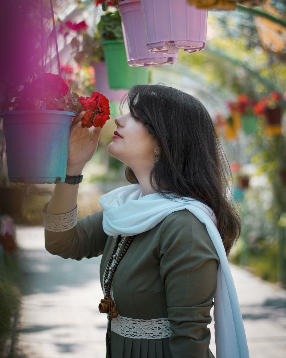 woman in green jacket holding pink plastic cup