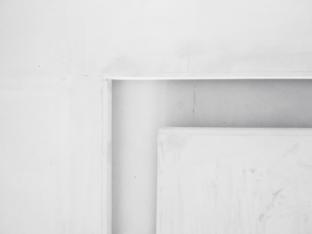 white wooden door on white concrete wall