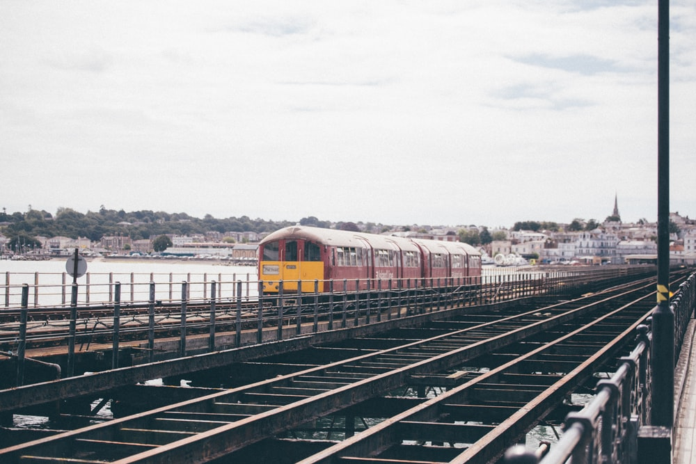 red and yellow train on rail during daytime