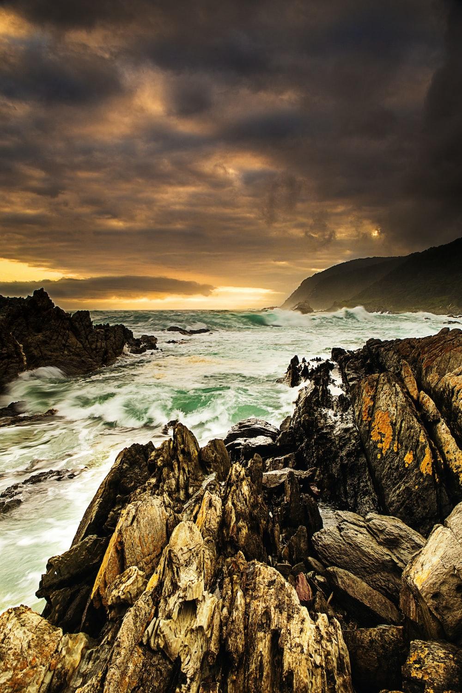 ocean waves crashing on rocky shore during sunset