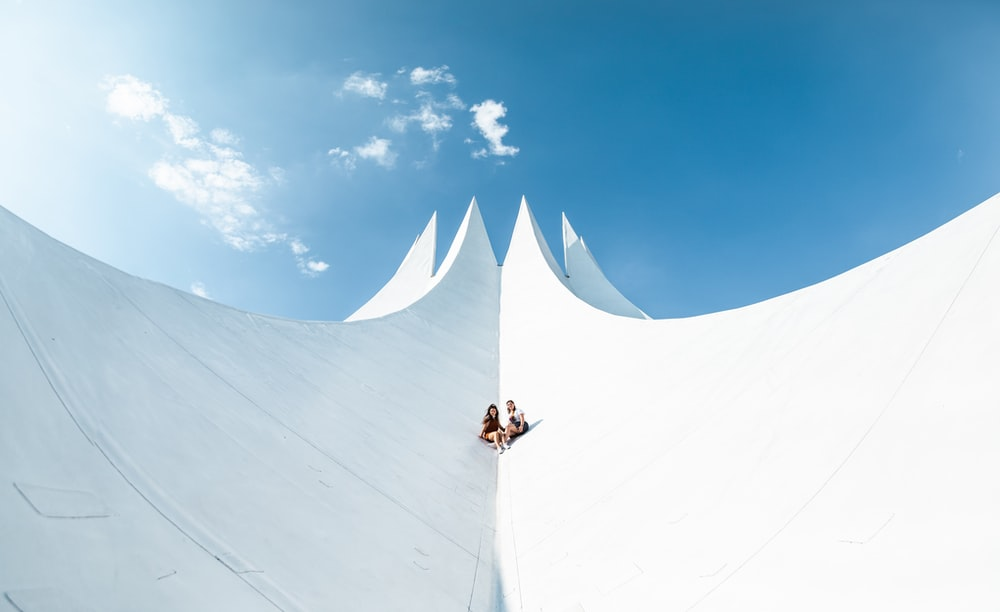 person in white shirt and black pants standing on white snow under blue sky during daytime