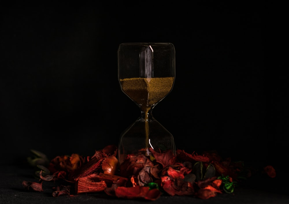 clear glass hour glass on red and yellow leaves