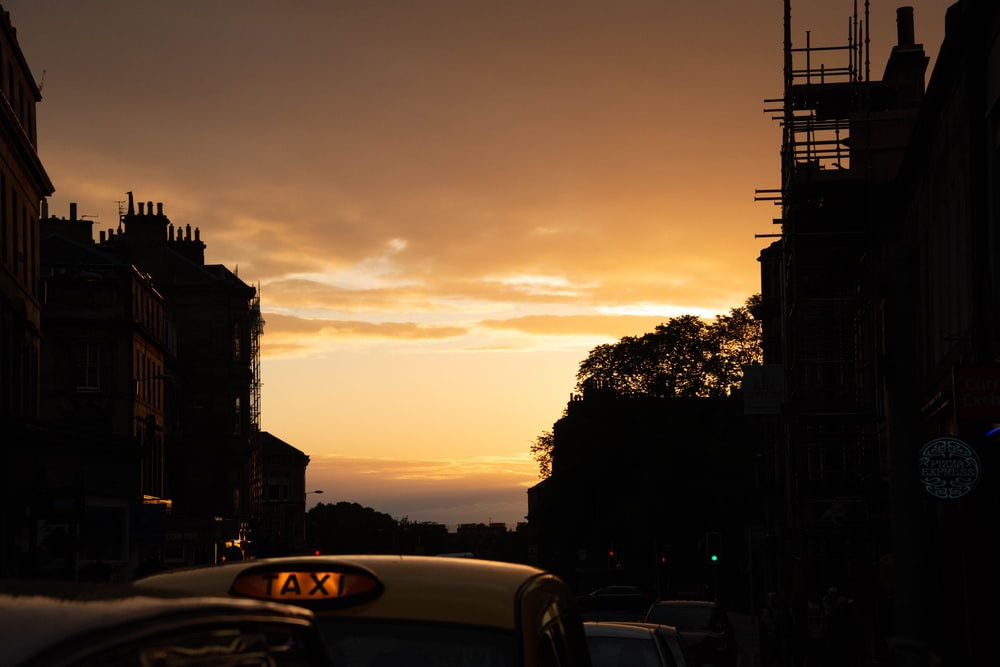 yellow taxi cab on road during sunset