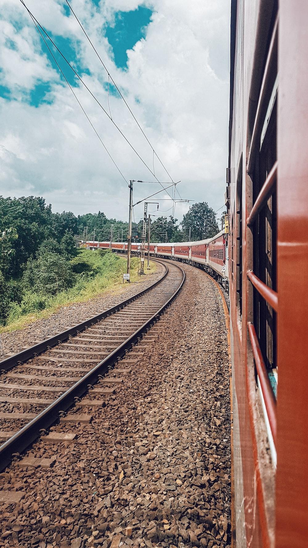 brown metal train rail near green trees during daytime