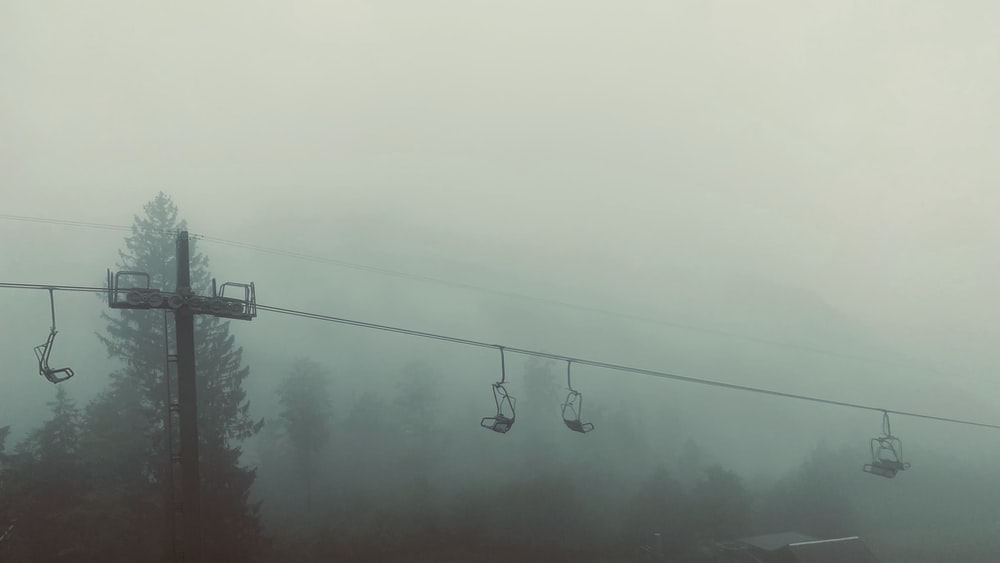 black cable cars under gray sky