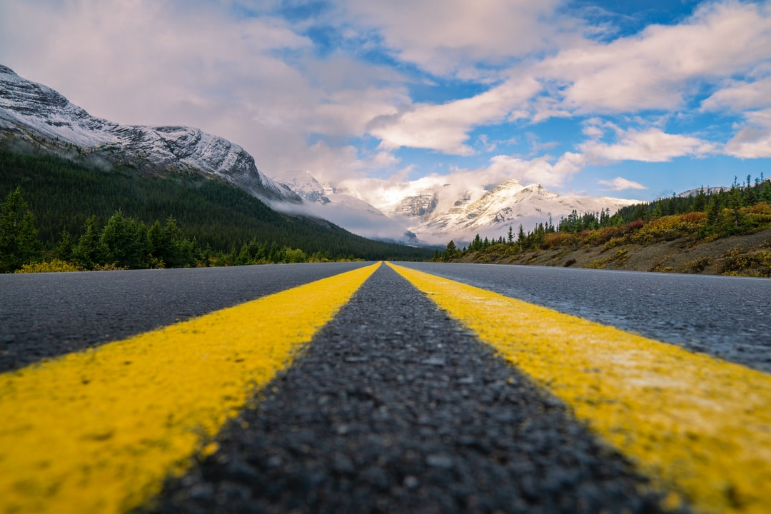 Close Up Yellow Lines On Epic Highway Into Mountains On Summer Road Trip