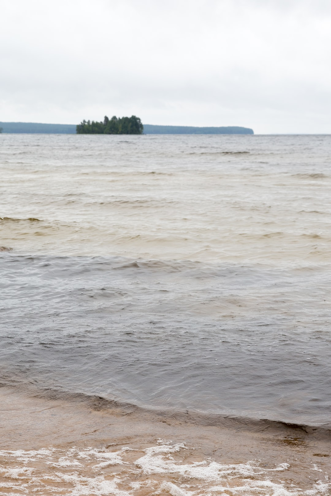 Sandy shore of the lake near the forest in Karelia