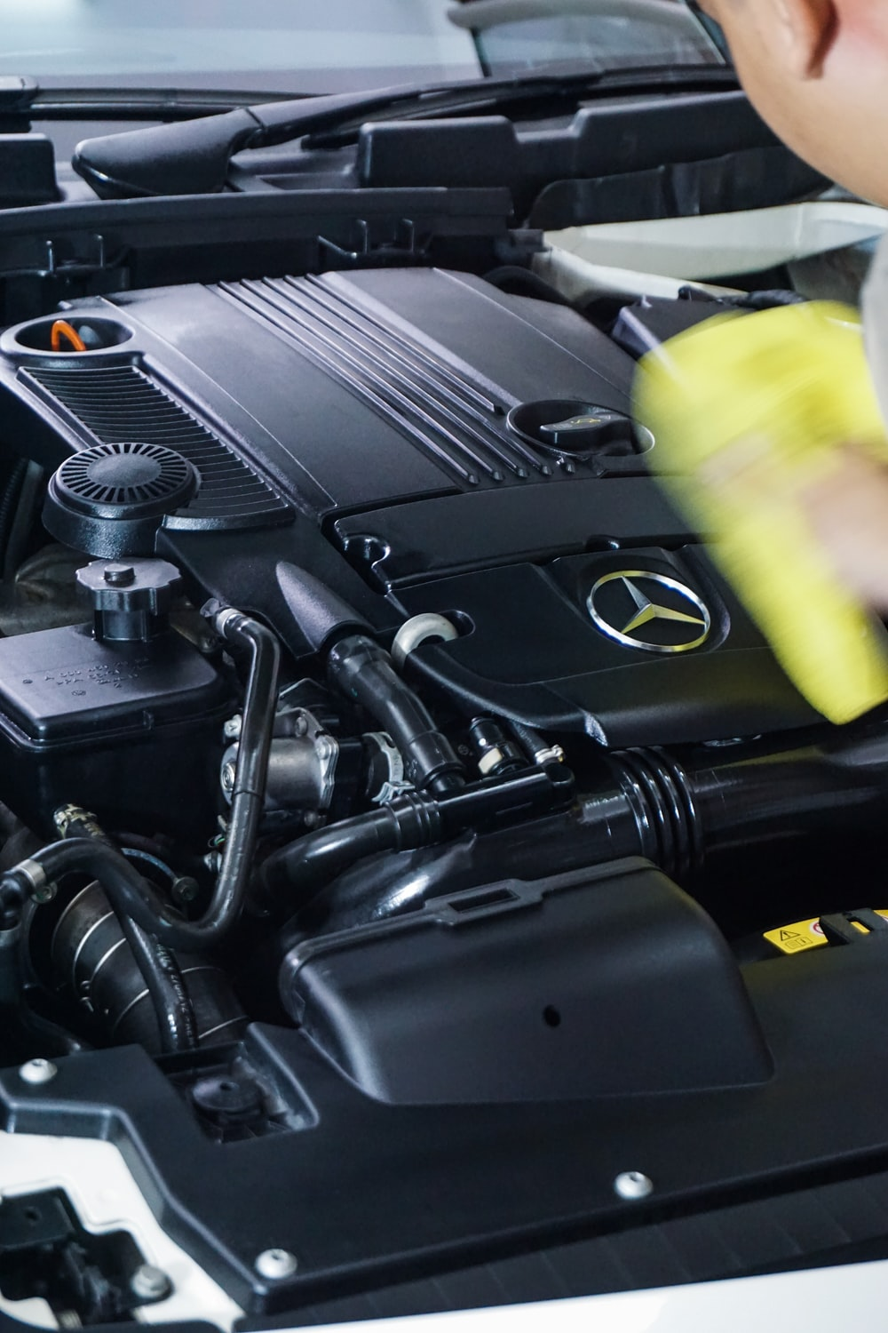 black car engine bay and yellow plastic cup