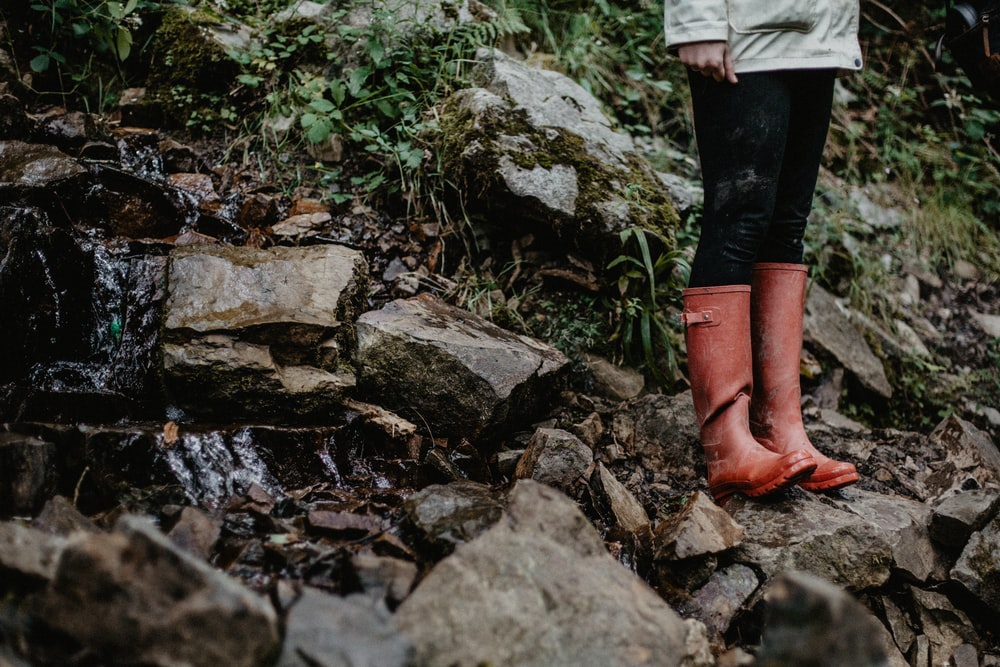 person in red leather boots standing on rocky ground