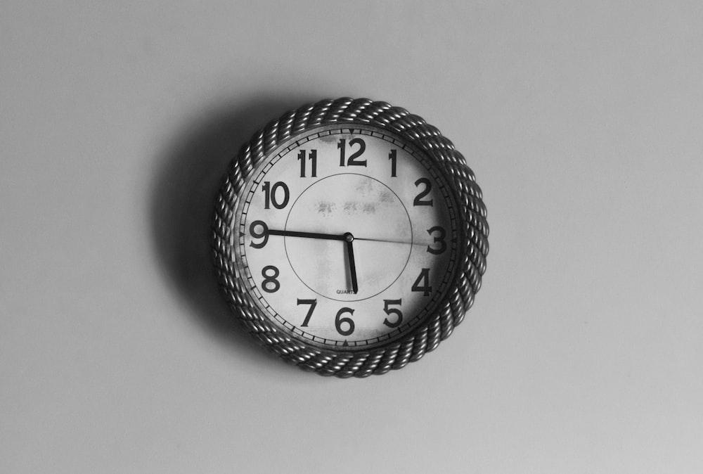 black and white analog wall clock at 10 10