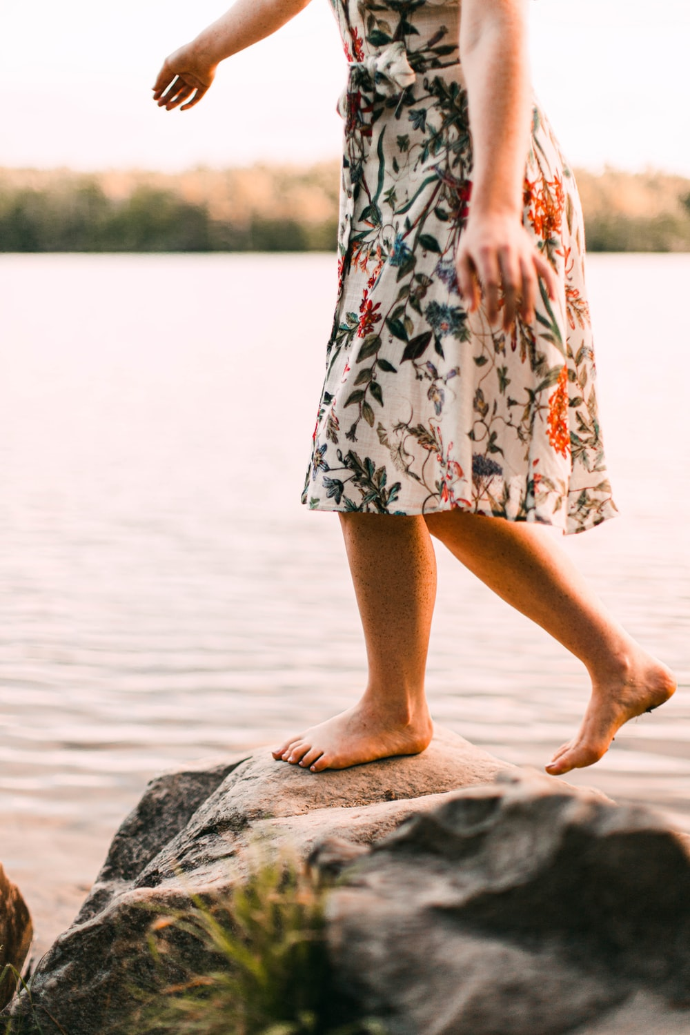 woman in white red and black floral dress standing on gray rock near body of water