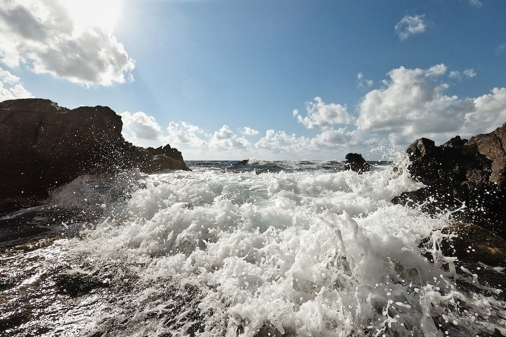 ocean waves crashing on brown rock formation under blue and white cloudy sky during daytime