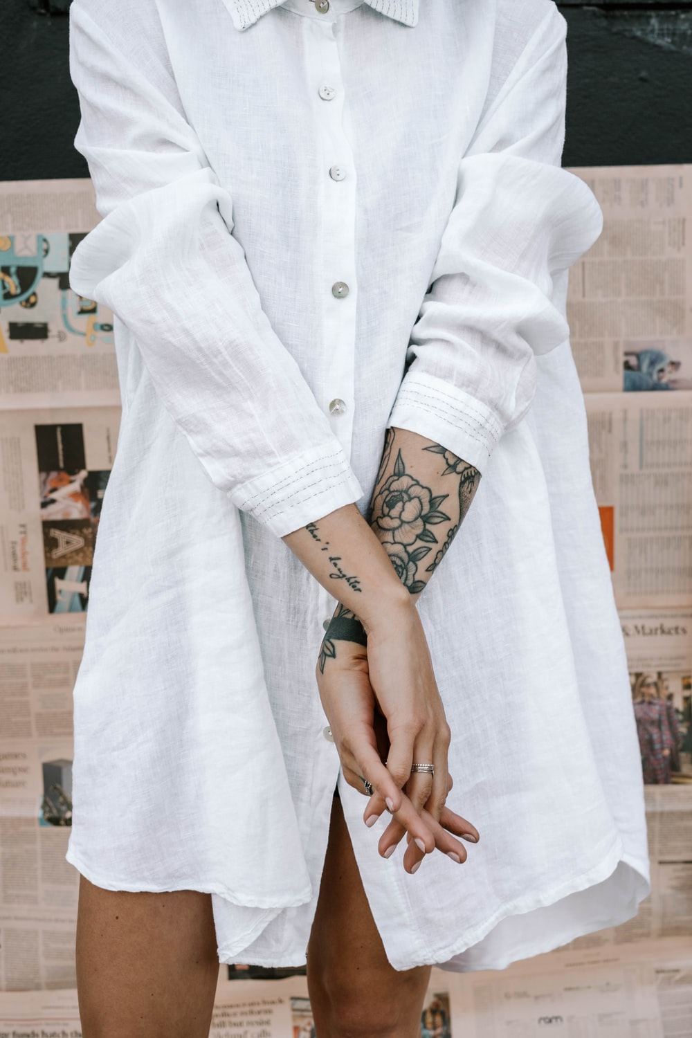 woman in white coat with black floral tattoo on left arm