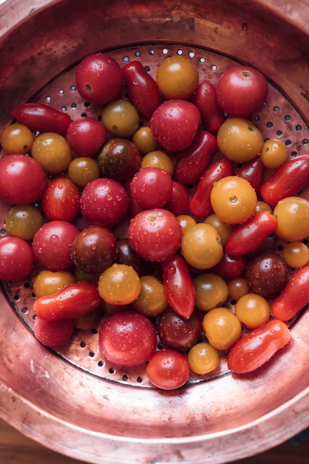 red and yellow round fruits on brown steel basket